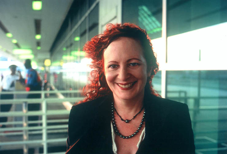 A woman with light skin and bright red, curly hair smiles brightly into the camera. She wears a dark blazer, two necklaces of dark beads and bright red lipstick. Wind blows her hair to her right shoulder, beyond which appears to be the exterior of an airport.