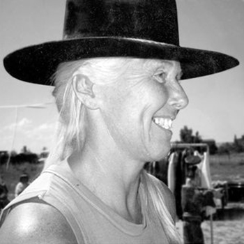 A black-and-white photograph of a light-skinned, smiling adult woman in profile wearing a black Western-style hat and tank top, her white hair pulled to the side. She stands in a field of sparse grass. Behind her are two people, a rack of clothing, furniture, and distant trees.