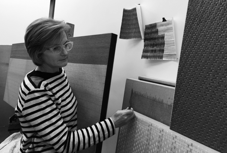 A black-and-white photograph of a light-skinned adult woman with short hair, stylish glasses, and a striped top, contemplating her many highly textured paintings that resembled magnified textile swatches. She thoughtfully holds a painting knife near one painting.