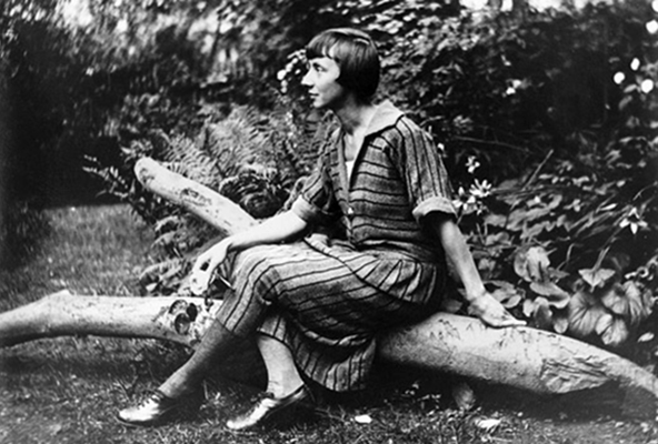 A black-and-white photograph of a light-skinned adult woman. Seated outdoors on a log in front of greenery, she is posed in profile with her body turned to the left of the composition. She wears a long striped dress and crosses her legs. She has short, dark hair cut in a bob.