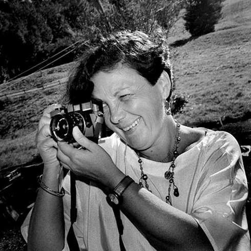 A black-and-white photograph of an adult woman with short, dark hair looking into the viewfinder of a small film camera. She is outdoors with grass behind her. She holds the camera with her right hand and focuses the lense with her left. She is smiling as she looks into it.
