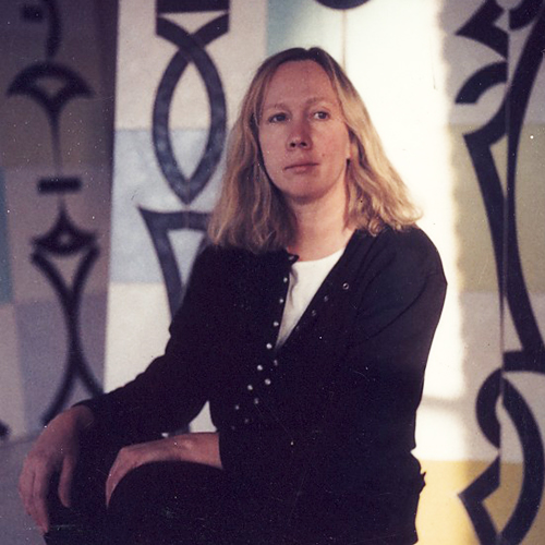 Color photo of a seated woman with her hands on her knees. She has shoulder-length blonde hair and light skin and looks past the camera. Behind her, abstract paintings on panels of yellow, white and blue covered in black symbols. A patch of sunlight lights the left side of her face.
