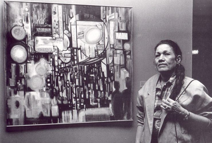 A black-and-white photograph of an adult woman with long dark hair in a braid. She wears a plaid shirt, jacket, large belt and hoop earrings. Her hand is touching her braid. She stands next to a painting which depicts an abstract street scene.