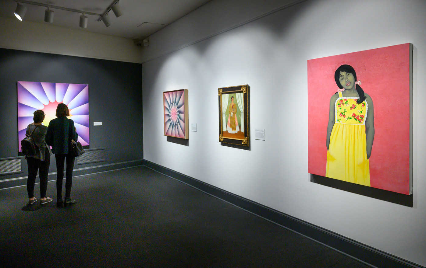 A partial view of an art gallery with four artworks on display, including a painted portrait of a young, pony-tailed medium-dark skinned girl in a yellow flowered dress against a pink background; a smaller portrait; and large abstract works with colorful shapes and gradients.