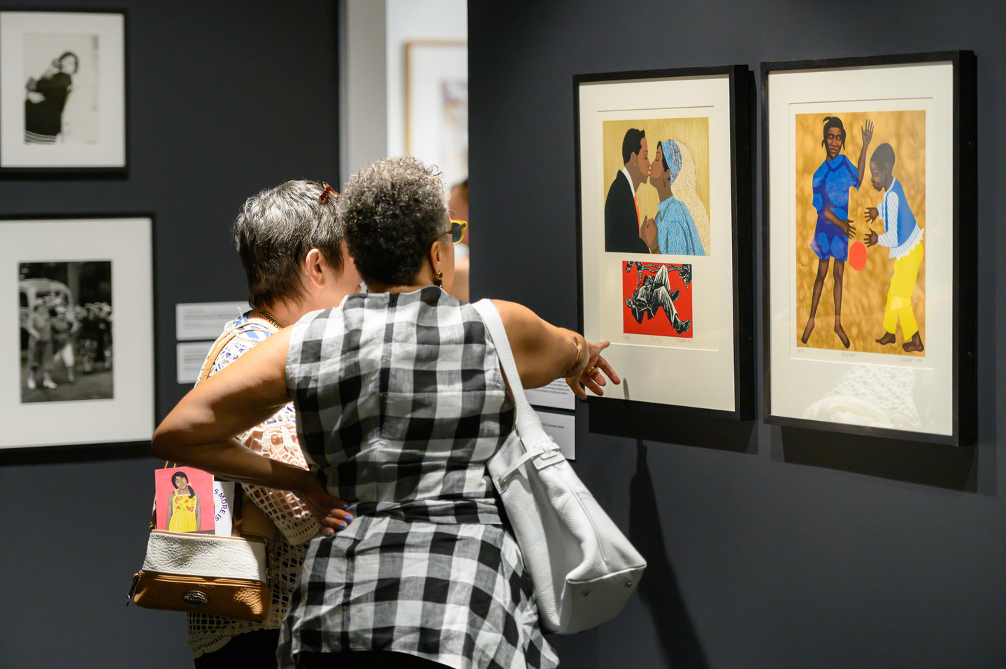 Two women with short gray hair look at brightly colored prints and point to details of the artwork.