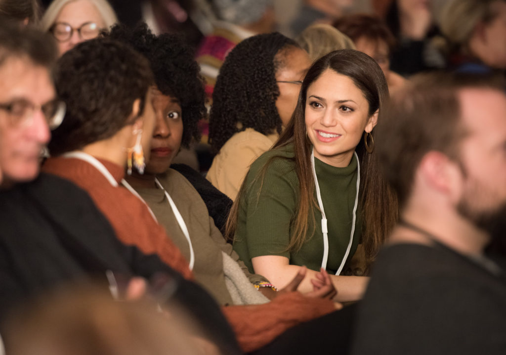 A medium light-skinned young adult smiles while listening to another adult speak a few seats over from her in a full auditorium.
