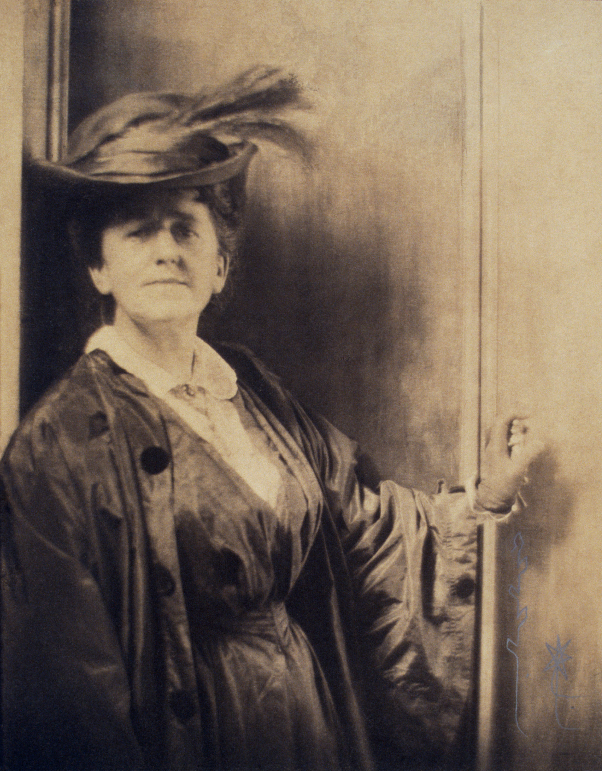 A sepia-toned photograph of a light-skinned adult woman. Standing against a wall, she dons a large black hat with a feather in the brim. She wears a dark dress with a white collared shirt and a long baggy dark coat. She places her left hand on the wall beside her.