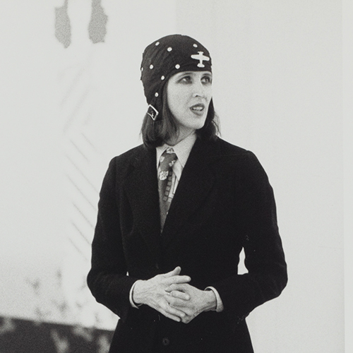 Black-and-white photograph of a light-skinned adult woman with medium-length dark hair, dark eyeliner and lipstick. She wears a dark blazer, light-color collared shirt, patterned necktie, and black cloth cap with white polkadots and airplane decal and a metal buckle.