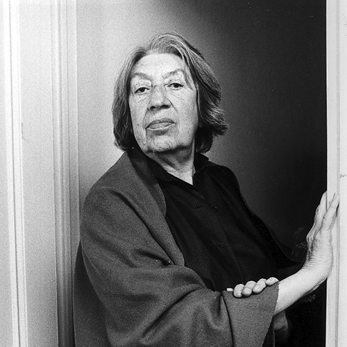Black-and-white photograph of an older light-skinned woman with short grey and white hair. She stands in a doorway, and rests her right hand against the door frame to her left and her left hand on her right forearm. She wears a dark blouse and shawl.