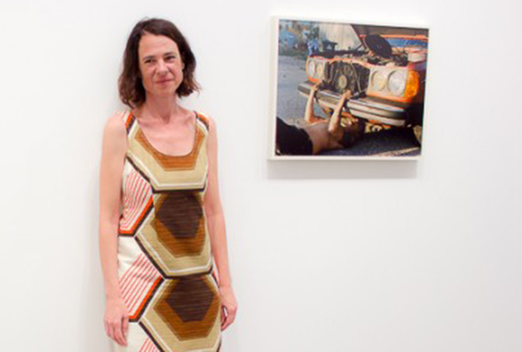 A light-skinned adult womand with bobbed brown hair stands against a white wall wearing a sleeveless dress with a colorful geometric print. On the wall behind her hangs a color photograph of a light-skinned person working outside under the hood of an old red car.