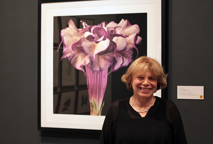 A light-skinned, adult woman with short, blonde hair grins in front of one of her photographs depicting a blossoming, purple datura flower against a black background.