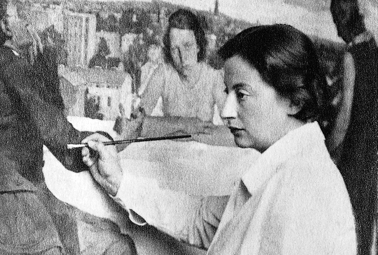 Grainy black-and-white photograph of a light-skinned adult woman with short dark hair. She stands in profile in front of a large painting of three figures around a table before a cityscape. She wears a white collared blouse and holds a brush in her right hand up to the painting