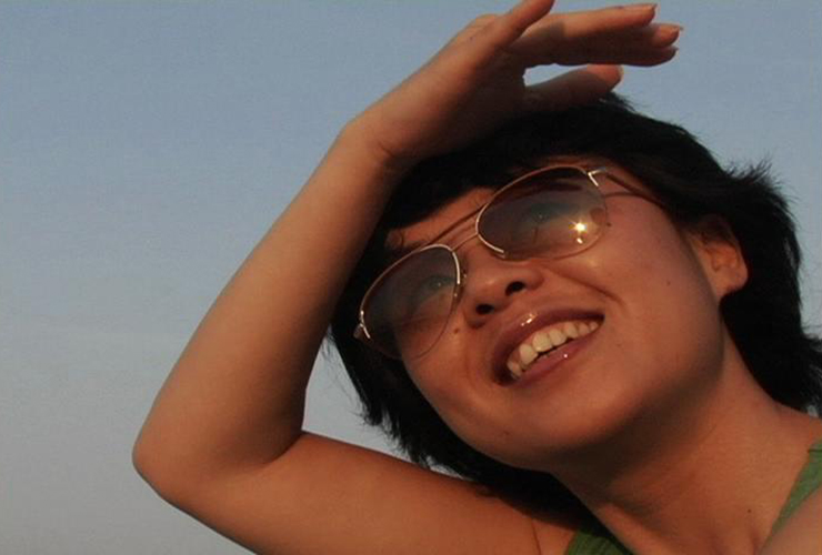A color photograph of a medium-brown skinned woman, wearing aviator sunglasses against a blue background. She smiles as she gazes upwards, shading her eyes with her hand. The sun glints on the sunglasses and her glossy lips.