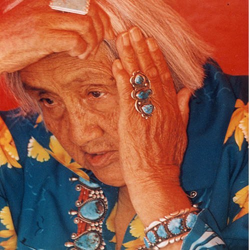 Color photograph of an older woman with short, white hair. Her medium-dark skin is lined, and she reaches her hands up to touch her hair. She wears large turqouise jewelry and a blue shirt with large yellow blossoms.