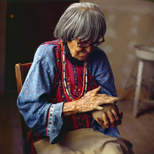 Photo of an older woman working a ball of clay that she holds in her hands. She has grey hair cut just below the ear, medium skin tone and wears a blue dress and beaded necklaces of white, blue, red and silver. She is engrossed in the clay, her movements practiced.