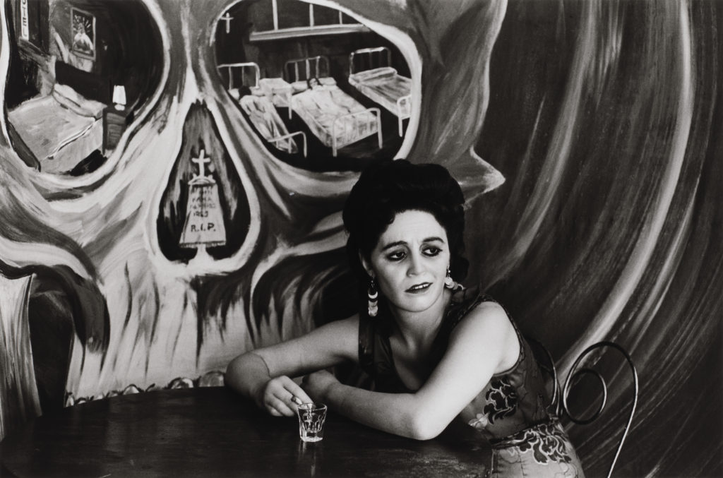 A light-skinned woman with heavy eye makeup leans over a round table, holding a cigarette next to an empty clear shot glass. A skull is painted in sweeping brushstrokes on the wall behind her, with a tombstone in the nasal cavity and hospital beds in the eye cavities.