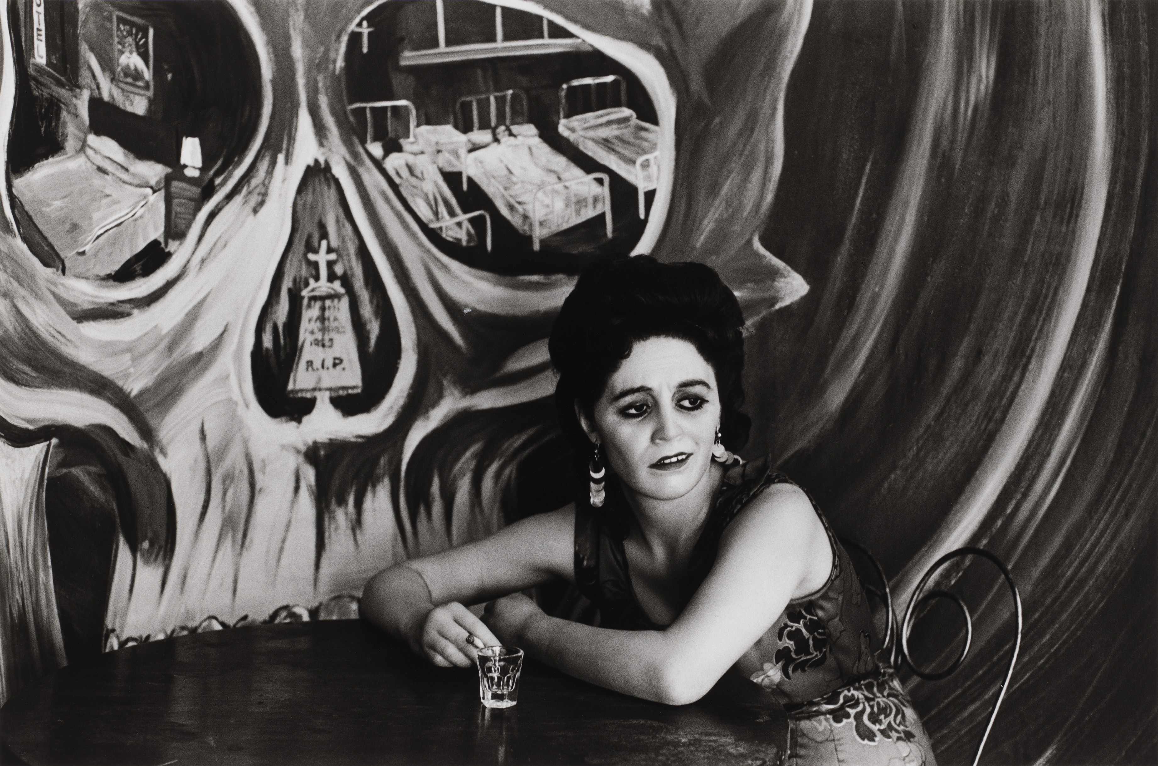 Black and white photograph of light skin toned woman with long dark hair sitting at a cafe table. On the wall behind her is a painted mural of a large skull with hospital beds visible in the eye sockets and a tombstone in the nasal cavity.
