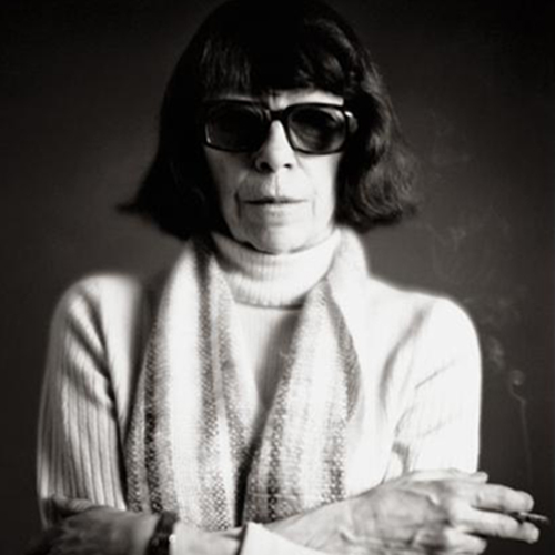 A black-and-white studio portrait of a light-skinned older woman with dark bobbed hair. She wears sunglasses, a light-colored turtleneck sweater, a striped scarf, and a watch. She stands with arms folded and holding a lit cigarette between her left index and middle fingers.