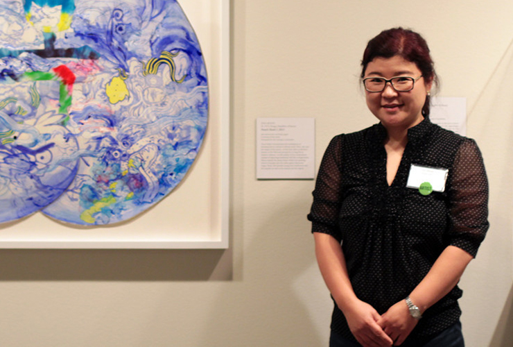A medium-light-skinned smiling adult woman with dark hair in a ponytail, clasps her hands in front of her. She wears a black dress with a name tag, glasses, and watch. On the white wall behind her is a colorful abstract painting and a label with unreadable text.