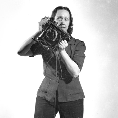 A black-and-white photograph of a light-skinned adult woman standing against a white backdrop and holding a large, antique camera in her hands at an angle. She gazes to the side and has dark, wavy hair and wears a collared, buttoned jacket and slacks.