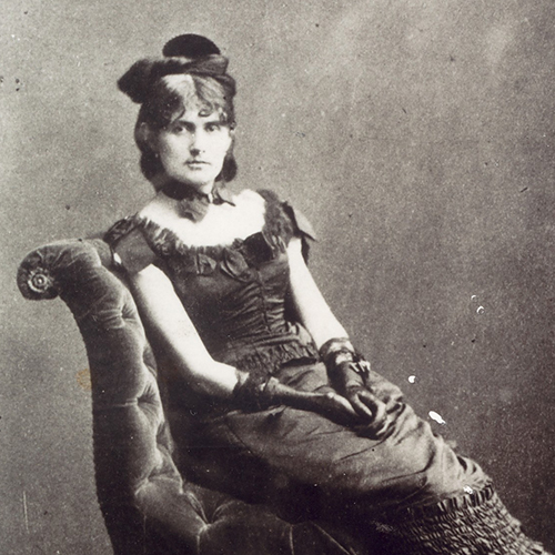 A black-and-white photograph of a light-skinned adult woman sitting upright in a luxurious velvet chair. Her dark hair is meticulously curled, and she wears a fascinator, a collar necklace with a bow, long gloves, and a long, sleeveless dress embellished with many frills.