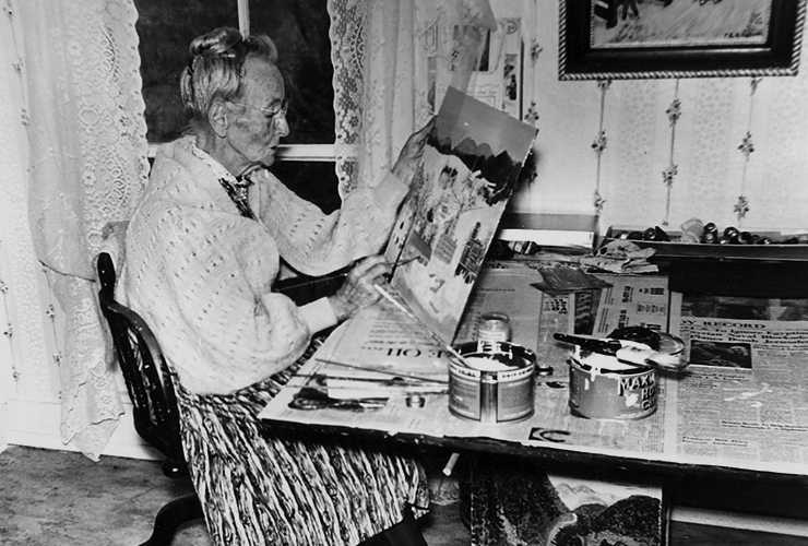 A black-and-white photograph of an older woman sitting at a table in front of floral wallpaper and a window with lace curtains. She holds up a canvas depicting houses and snow in her left hand. In her right hand, she holds a small paintbrush to the canvas.