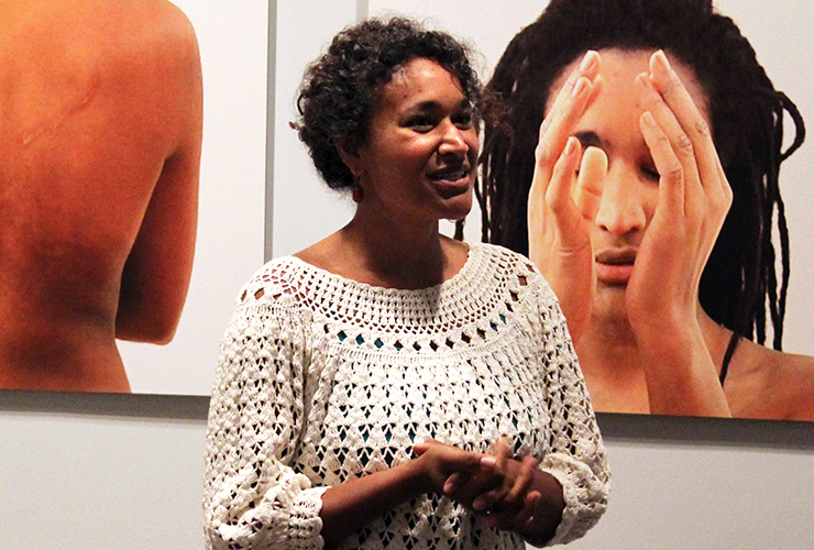 A medium-dark-skinned adult woman with short dark curly hair, wearing a white crochet top, stands with hands clasped in front of her. On the wall behind her are two large color photographs of medium-skinned adult women.