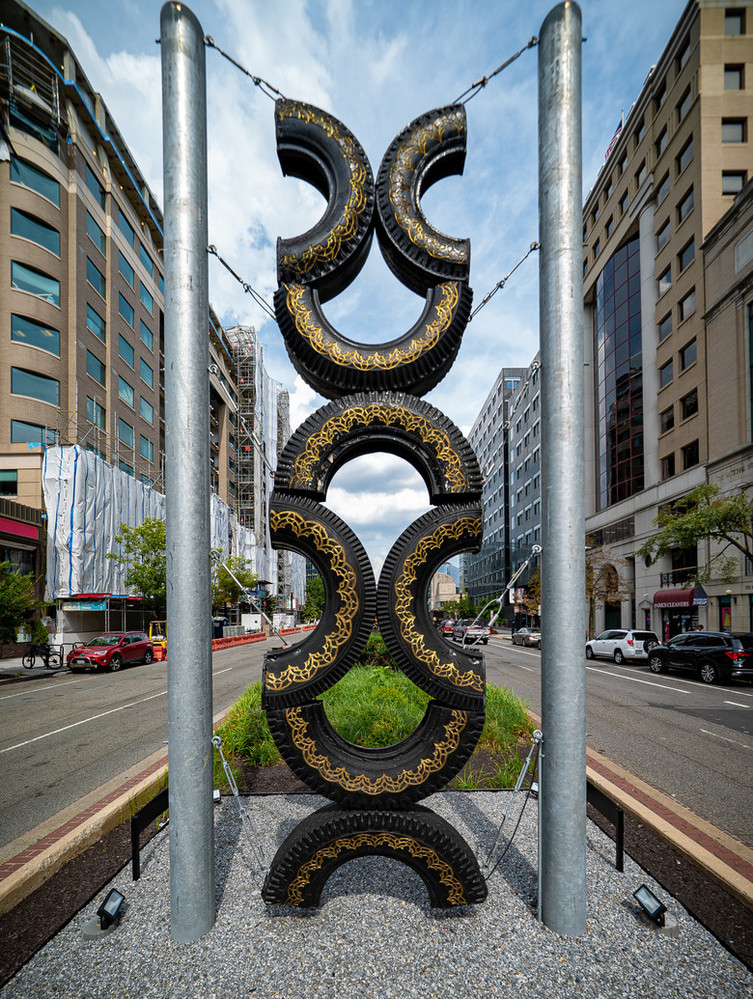 Large outdoor sculpture installed in the middle of a street made of four car tires cut in half and attached to one another in a column, adorned with details in gold paint.