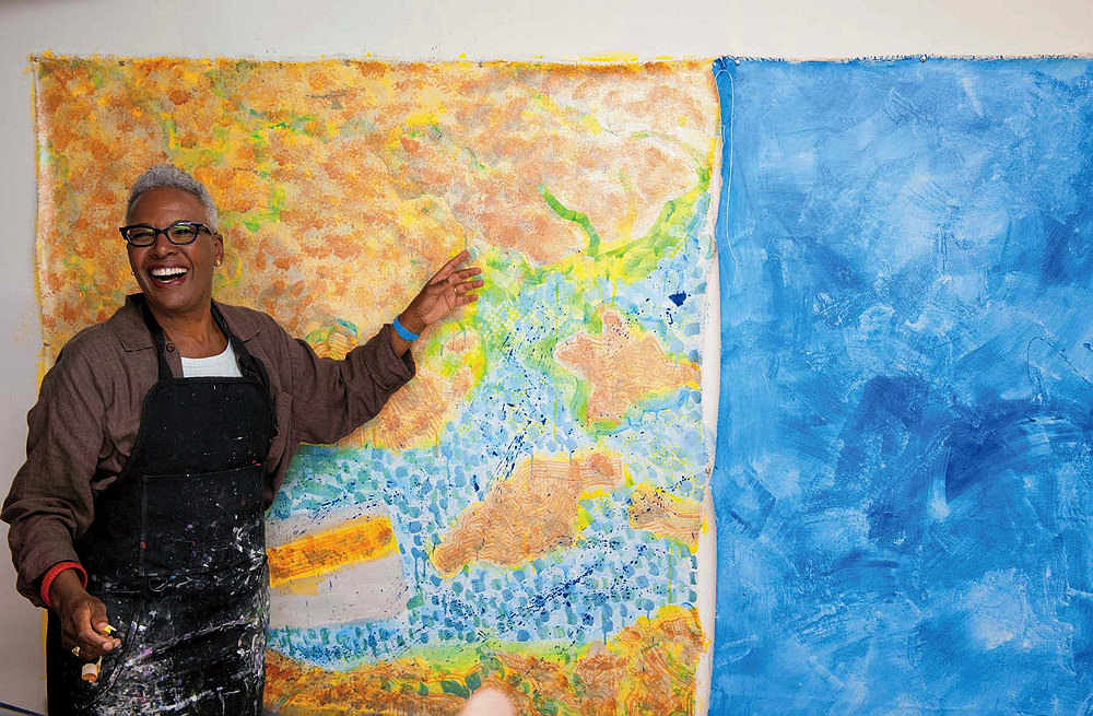Nell Irvin Painter stands in front of one of her works smiling in a paint-stained smock.