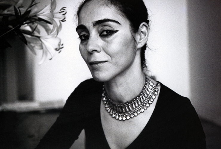 Black and white photo of a woman sitting next to a vase of lillies. Her eyes are lined in thick black pencil, which matches her dark brows. Her tiered metal necklace and dark v-neck shirt accenuate the skin of her chest. Her dark hair is pulled back and she smiles slightly.