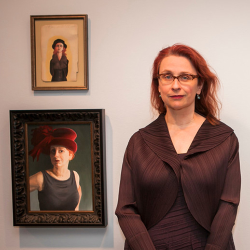 A light-skinned adult woman smiles while standing against a white wall beside two paintings that resemble her in theatrical costumes. She has long red hair, and wears glasses, earrings, and a brown jacket over a matching brown dress with subtle, organic stripes on them.