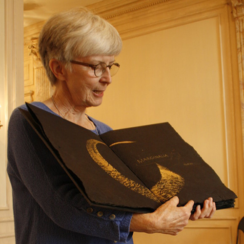 An older light-skinned woman with short white hair wears glasses and a long-sleeve blue top. She stands inside, holding open a large black book with an abstract gold design printed across two pages and unreadable gold writing.