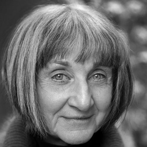 A black-and-white photograph of a light-skinned adult older woman seen from the chin up. She has a salt-and-pepper bob haircut and wears a dark turtleneck.