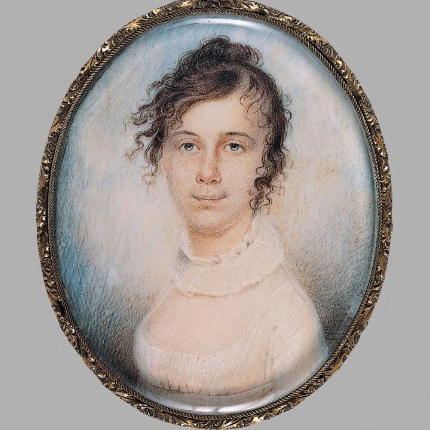 An oval painting in a delicately detailed frame with a protective resin cast over it depicting a light-skinned adult woman smiling gently. She wears a white dress and slightly frilled collar, and her curly dark hair is pulled up but also appears slightly windswept.