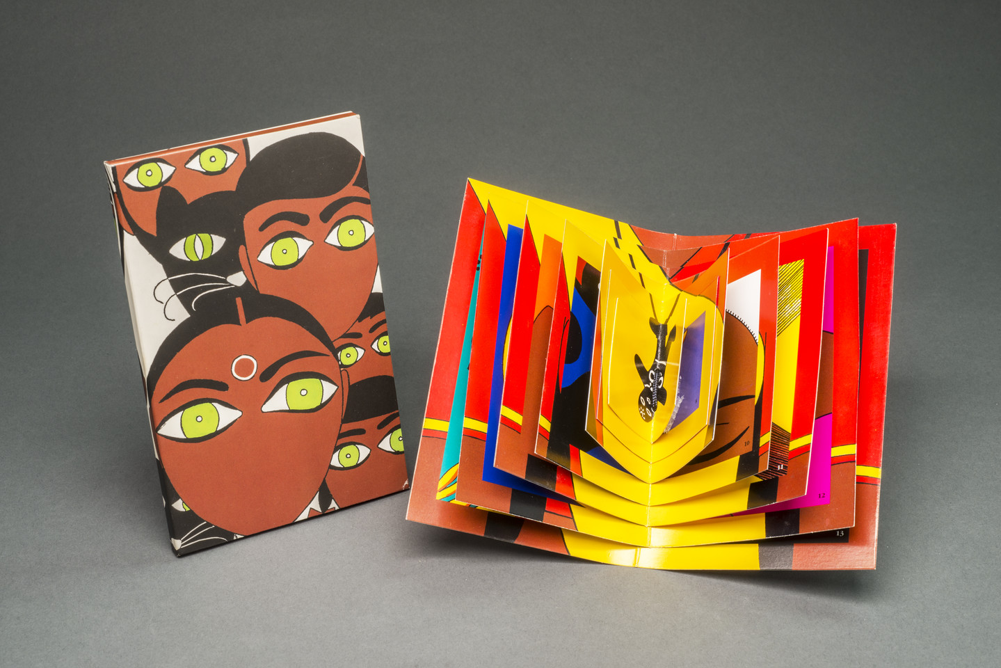 A brightly colored book displayed open whose pages decrease in size toward the center. To the left, a vertical rectangle on which is depicted five stylized faces with black hair, medium-dark skintone, green eyes, and no mouths. A black cat with green eyes is also among the faces.