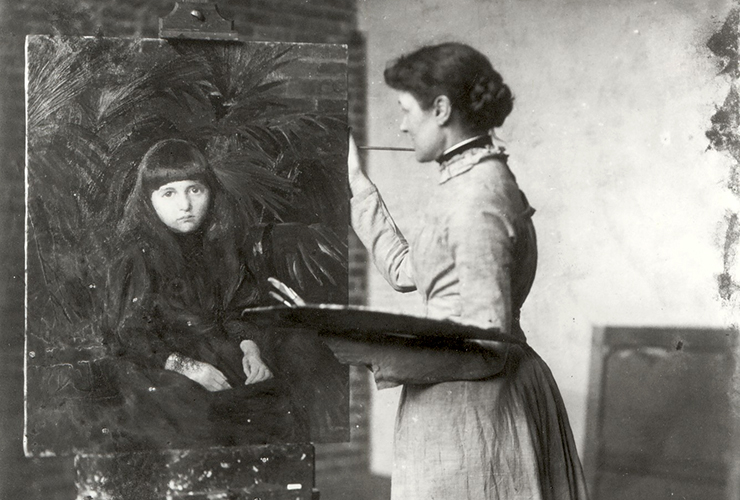 Black-and-white interior photograph of a light-skinned adult woman in profile with dark hair in a bun and a light-color dress. She stands in front of an easel and holds a palatte and brushes in her left hand. She rests her right hand on a painting of a light-skinned young girl.
