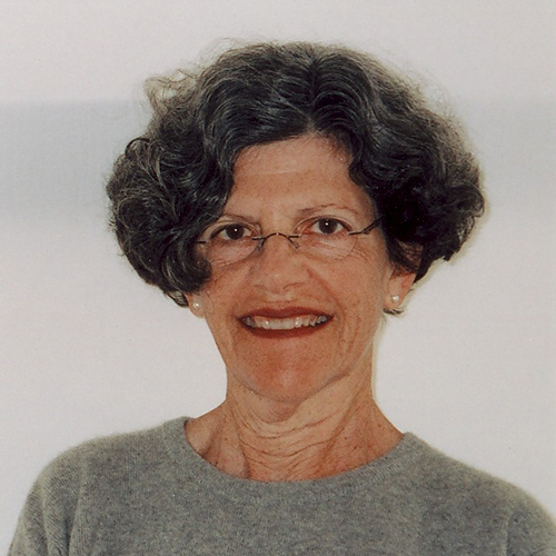 An older light-skinned woman with short, dark, curly hair looks directly at the viewer. Posed from the chest up against a light grey background, she wears a darker grey sweater, eye glasses, pearl earrings, and lipstick.
