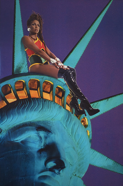 A print of a closeup of the Statue of Liberty's face/crown with a black woman wearing thigh high shiny black boots and a colorful leotard sitting atop, looking out into the distance.