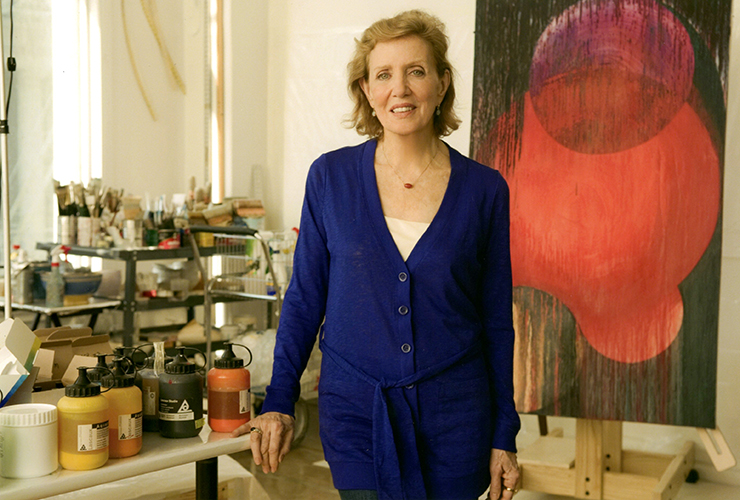 A light-skinned older woman stands in the middle of an art studio. She has short, light colored hair and wears a long blue cardigan. Next to her is a table with paint bottles on it. Behind her are carts with paint brushes and art supplies, and a large abstract red and black painting on an easel.