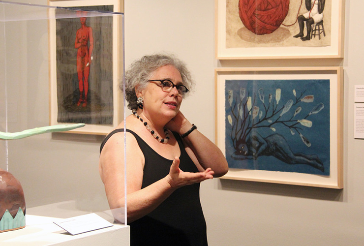 A light-skinned, adult woman speaking with one hand extended and the other touching her neck in a white gallery filled with her colorful artworks depicting African-American women. She has curly gray hair, glasses, and wears a simple, black, sleeveless top and a necklace.