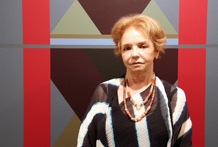 A light-skinned older woman with short, light brown hair stands in front of an abstract painting. She wears a black and white striped shirt with two beaded necklaces. The painting behind her depicts grey and red rectangles framing grey, brown, and green triangles.