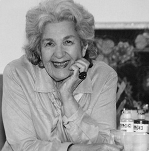 Black and white photo of a woman shot from the waist up. She rests her chin in her right hand, her right elbow propped on a table next to bottles of paint. She smiles with her whole face and her grey hair is brushed back. She wears a light blouse and large cocktail ring.