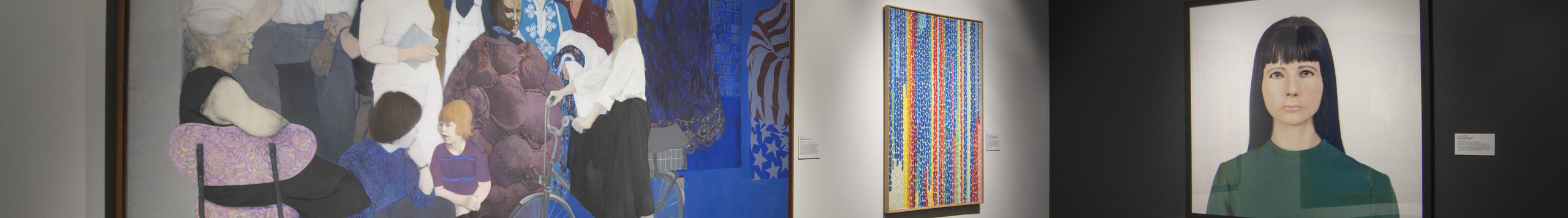 Gallery view of two large-scale, brightly colored works of art on a white wall and a wall-size portrait of a light-skinned woman on the adjacent, dark gray wall.