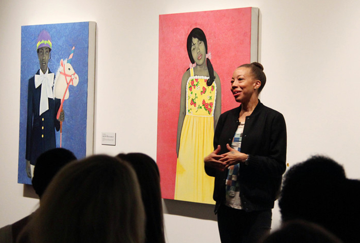 Amy Sherald—a medium skin-toned adult woman—stands and speaks to a crowd in a gallery beside her striking portraits depicting individuals with gray skintones against vibrant, solid-colored backgrounds. She smiles, her dark hair pulled tightly into a bun, and wears mostly black.