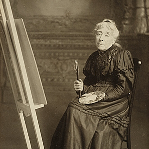 Black-and-white studio portrait of a light-skinned older woman white hair pulled back. She sits in a chair next to an easel and holds a palatte and brushes. She wears a high-neck, long-sleeve, dark-color long dress.