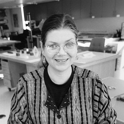 A black-and-white photograph of a smiling Pamela Spitzmueller, a light-skinned woman with eyeglasses, in a conservation lab. Her hair is parted in the middle and pulled back, revealing dangling earrings. She wears an ikat-woven jacket.