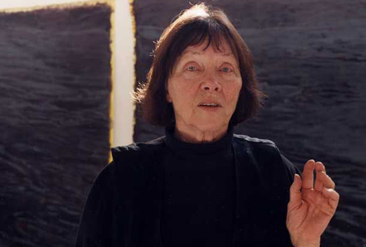 Photo of a light skinned woman against an abstract background. Shot from the chest up, her left hand is slightly raised in a wave. Short, brown hair frames her face, her mouth slightly open. Her eyebrows are raised, as if the image was taken when she was mid-sentence.
