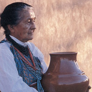 Color photo of a woman holding a large glazed pot. Seated against a sunlit wall, her dark hair is pulled back and she wears a white blouse with a color handkerchief and layers of necklaces with blue, red and black beads. She gazes into the distance, a calm expression on her face.