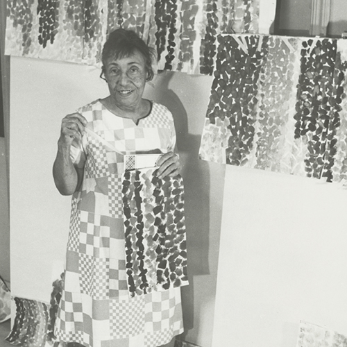 A black-and-white photograph of an older adult woman wearing a dress with square patterns resembling a quilt. She smiles, surrounded by her paintings, holding one herself. The paintings feature different colored, thick, similarly shaped brushstrokes that create vertical stripes.