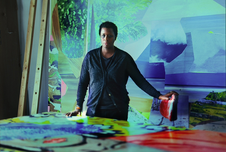 A woman with a dark skin tone and short black hair stands behind a large table covered in a painting. Her dark clothing stands out against the rich blues, greens, reds and yellows of the room she is in. Her left hand rests on a stool covered in red paint.
